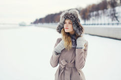 Portrait of a beautiful woman dressed a coat and fur hat. In the winter field Stock Image