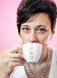 Portrait of beautiful woman drinking coffee. Studio shoot over pink background Royalty Free Stock Image