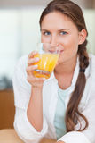 Portrait of a beautiful woman drinking juice. In her kithen Royalty Free Stock Photo