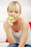 Portrait of beautiful woman eating an apple stock images