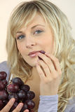 Portrait of a beautiful woman eating grapes Royalty Free Stock Image