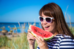 Portrait of beautiful woman eating watermelon on the beach Royalty Free Stock Photos