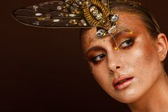 Portrait of a beautiful woman with expressive creative make-up in bronze and with a decoration on her head royalty free stock photos