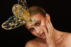 Portrait of a beautiful woman with expressive creative make-up in bronze and with a decoration on her head royalty free stock image