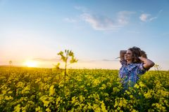 Portrait of beautiful woman in a field of coleseed in bloom. Young woman in a field of Cole seed in bloom in sunset. Freedom and ecology concept stock image