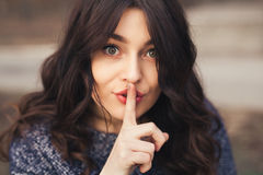 Portrait of beautiful woman with finger on lips. Stock Photos