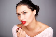 Beautiful woman with flawless complexion applying red lip gloss. Portrait of beautiful woman with flawless complexion applying red lip gloss royalty free stock image