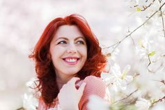 Portrait of a beautiful woman with flowering tree. Portrait of a beautiful woman in a flowering magnolia tree Royalty Free Stock Photography