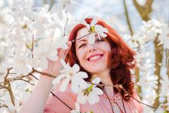 Portrait of a beautiful woman with flowering tree. Portrait of a beautiful woman in a flowering magnolia tree Royalty Free Stock Photo
