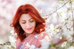 Portrait of a beautiful woman with flowering tree. Portrait of a beautiful woman in a flowering magnolia tree Stock Image