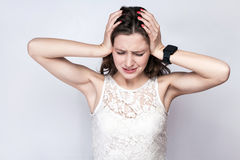 Portrait of beautiful woman with freckles and white dress and smart watch with headache pain on silver gray background. Royalty Free Stock Photography