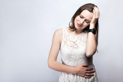 Portrait of beautiful woman with freckles and white dress and smart watch with stomach pain on silver gray background. Stock Photography