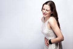 Portrait of beautiful woman with freckles and white dress and smart watch with stomach pain on silver gray background. Healthcare and medicine concept Royalty Free Stock Images