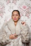 Portrait of a Beautiful Woman in Fur Coat. Against floral background Stock Photos