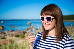 Portrait of beautiful woman with glass of champagne on the beach. Portrait of young beautiful woman with glass of champagne on the beach royalty free stock photography