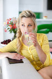 Portrait of a beautiful woman with a glass of water in the kitchen Royalty Free Stock Photo