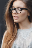 Portrait of beautiful woman in glasses on gray background Royalty Free Stock Photos