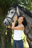 Portrait of beautiful woman and gray horse in garden Stock Images
