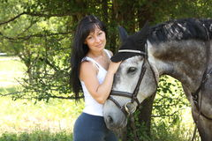Portrait of beautiful woman and gray horse in garden Stock Photos