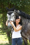 Portrait of beautiful woman and gray horse in garden Stock Image