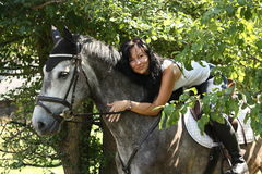 Portrait of beautiful woman and gray horse in garden Stock Photography