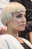 Portrait of beautiful woman at the hair fashion show. Kiev, Ukraine - September 18, 2014: A blond model gets ready backstage for the hair fashion show at royalty free stock photography