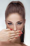 Portrait of beautiful woman with hand on lips over gray background Royalty Free Stock Images