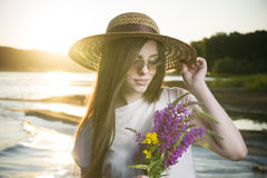 Portrait of a beautiful woman in a hat on a background of a sunset Stock Image