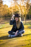 Portrait of a beautiful woman in hat on the park sitting on the Royalty Free Stock Image