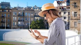 Portrait of beautiful young woman in hat using mobile phone on stadium at hot summer day royalty free stock image
