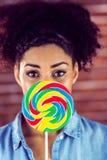 Portrait of a beautiful woman hiding behind a giant lollipop Stock Image