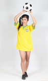 Portrait Beautiful woman hold ball over her head with wearing Br. Portrait Beautiful woman hold ball over  head with wearing Brazil football top Royalty Free Stock Photography