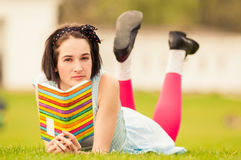 Portrait of beautiful woman holding a book and standing outside. On grass as relaxation concept Royalty Free Stock Image