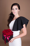 Portrait of beautiful woman holding box with red flowers Royalty Free Stock Photography