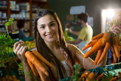 Portrait of beautiful woman holding bunch of fresh carrots in organic section Stock Photography