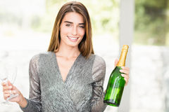 Portrait of beautiful woman holding champagne bottle and glass Royalty Free Stock Image