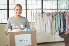 Portrait of beautiful woman holding clothes donation box Stock Photo