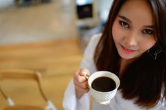 Portrait of beautiful woman holding a cup of coffee in her hand in blur background coffee shop stock photo