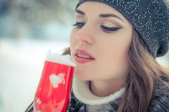 Portrait of a beautiful woman holding a glass of champagne with snow inside royalty free stock images