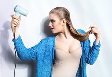 Portrait of beautiful woman holding hair dryer Royalty Free Stock Image