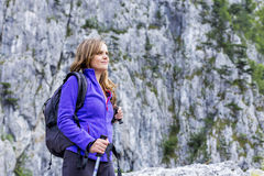 Portrait of a beautiful woman holding hiking pole while climbing Royalty Free Stock Photo