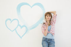 Portrait of beautiful woman holding paint brush with hearts painted on wall Royalty Free Stock Photo