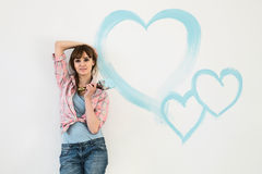 Portrait of beautiful woman holding paint brush with hearts painted on wall Royalty Free Stock Image