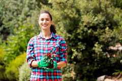 Portrait of beautiful woman holding potted plant. Against trees at lawn stock photography