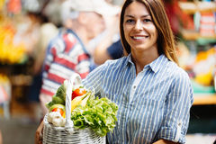 Portrait of beautiful woman holding shopping basket. At marketplace Stock Images
