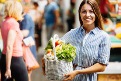 Portrait of beautiful woman holding shopping basket. At marketplace Royalty Free Stock Photos