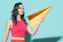 Portrait of a beautiful woman holding a yellow paper airplane. Royalty Free Stock Photos
