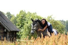 Portrait of beautiful woman on horse near the barn Royalty Free Stock Photos