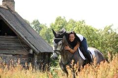 Portrait of beautiful woman on horse near the barn Stock Photo