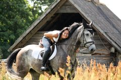 Portrait of beautiful woman on horse near the barn Stock Photos